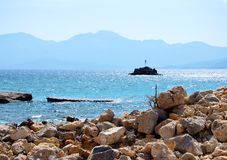 The blue horizon. The sun reflected in the coastal rocks. The mountains on the horizon are tight blue haze. It looks like it is here and converging story true Royalty Free Stock Photography