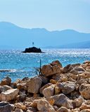 The blue horizon. The sun reflected in the coastal rocks. The mountains on the horizon are tight blue haze. It looks like it is here and converging story true Stock Image