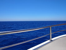 Blue horizon and clear sky. As seen behind the gunwale of a boat royalty free stock images