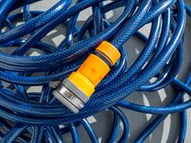 Blue Hose pipe and yellow adapter. Curled up blue hose pipe and yellow tap adapter royalty free stock images