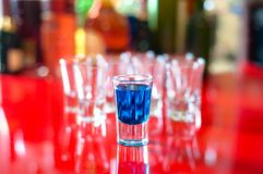 Blue hot alcoholic drink in shot glass on bar Royalty Free Stock Images