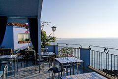 Blue hotel terrace on the coast below the volcano Etna Stock Photos