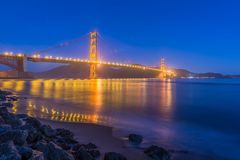 Blue hour from Fort Point. During low tide it is possible to access the rocky beach and photograph the iconic golden gate bridge at blue hour, as it casts its stock photo