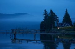 Blue Hour Harbour Reflections. Home overlooking harbour surrounded by fog, mountains and high trees. The scenery has a beautiful blue hue with reflection in the Stock Photo