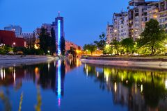 Blue hour light reflections in the city, on Dambovita river, in Bucharest, Romania. Tall building Chamber of Commerce and Industry. Of Romania in center-left royalty free stock images