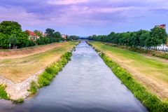 Blue hour Nisava river and promenade in Pirot with silky, blurred motion water, cloudy sky royalty free stock image