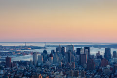 Blue hour over Downtown Manhattan and Verrazano Bridge, NYC. Aerial view of Downtown Manhattan and Wall Street and the Financial District's skyscrapers and royalty free stock image