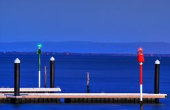 Blue hour photo of a jetty with Warning lights for boats. stock photos