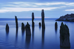 Blue hour sea landscape. As old barnacle covered posts pertrude artistically from the ocean water Royalty Free Stock Image