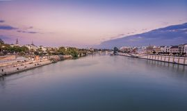 Blue Hour vew of seville and torre del oro from the triana bridge stock image
