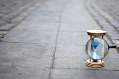 Blue hourglass and magnifying glass on stone pavement. Measuring time with blurred background Royalty Free Stock Photo