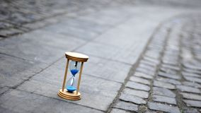 Blue hourglass on stone pavement. Measuring time with a curved blurred shape in background Stock Image