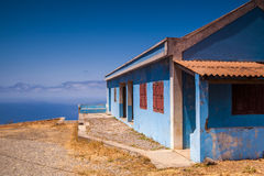Blue house. At the coast with the sea and a blue sky in the background Royalty Free Stock Images