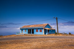 Blue house. At the coast with the sea and a blue sky in the background Stock Photo