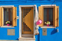 Blue house with flowers on sills in Burano, Venice.  Stock Photography