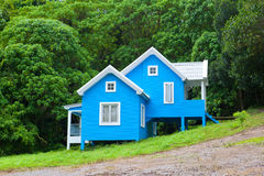 Blue house in forest royalty free stock photos