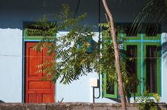 Blue house with a green window and a red door stock photography