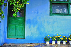 Blue house with green wooden window and door. And yellow flowers Stock Photos
