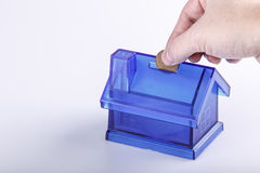 Blue House Money Box with man hand and coin on White Background Stock Photo