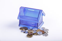 Blue House Money Box on White Background. With coins Stock Images