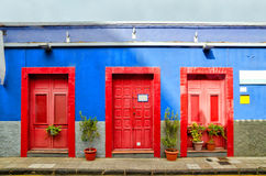 Blue house with three red doors in the old Town of San Cristobal de La Laguna. Stock Photos