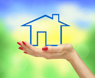 Blue house in woman hand over bright blurred nature background Stock Photos