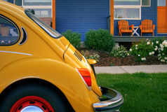 Blue house with wooden chairs and yellow bug Stock Photos