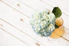 Blue hydrangeas in a vase. Hydrangeas in a vase on wood floor upper left focused on vase orange vase Stock Photography
