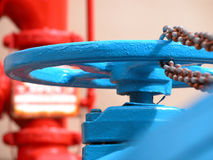 Blue Hydrant. A blue water hydrant with a rusted chain and a red meter in the background Stock Photography