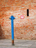Blue hydrant. A blue hydrant with red brick wall in the background Stock Photography