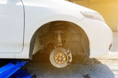 Blue hydraulic car floor jacks lift cars to change flat tires on the road. Wheel wrench placed nearby. stock photos