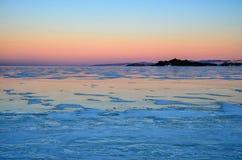 Blue ice of Baikal lake under pink sunset sky stock image