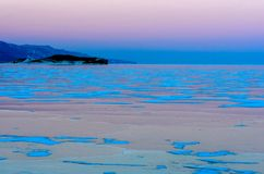 Blue ice of Baikal lake under pink sunset sky stock photography