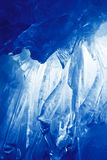 Blue Ice cave. Covered with snow and flooded with light stock images