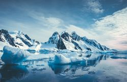 Blue Ice covered mountains in south polar ocean. Winter Antarctic landscape. The mount`s reflection in the crystal clear water. The cloudy sky over the massive royalty free stock photos