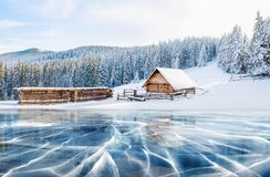 Blue ice and cracks on the surface of the ice. Frozen lake under a blue sky in the winter. Cabin in the mountains. Mysterious fog. Carpathians. Ukraine, Europe Royalty Free Stock Photos