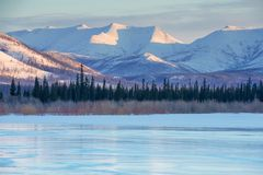 Blue ice of the frozen lake at morning. Winter landscape on the mountains and the frozen lake in Yakutia, Siberia, Russia. stock image