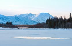 Blue ice of the frozen lake at morning. Winter landscape on the mountains and the frozen lake in Yakutia, Siberia, Russia. royalty free stock images