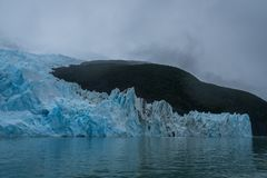 Blue ice of glacier reflecting in water stock image