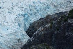 Blue ice of glacier surrounding rugged stone mountain Royalty Free Stock Image