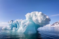 Blue ice iceberg floating in the arctic waters of Svalbard. Blue ice iceberg, formed when a glacier calves, floating in the arctic waters of Svalbard, a royalty free stock photo