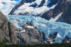 Blue ice mountain glacier. Vertical mountain glacier. Blue ice among dark rocks in the high mountains, Patagonia landscape Stock Images