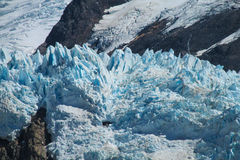 Blue ice mountain glacier. Vertical mountain glacier. Blue ice among dark rocks in the high mountains, Patagonia landscape Royalty Free Stock Photos