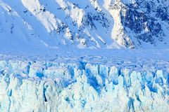 Blue ice and mountain. Winter Arctic. White snowy mountain, blue glacier Svalbard, Norway. Ice in ocean. Iceberg twilight in North. Pole stock photography