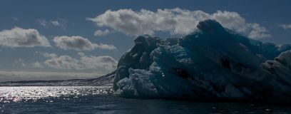 Blue iceberg floating in backlit Arctic sea Stock Images