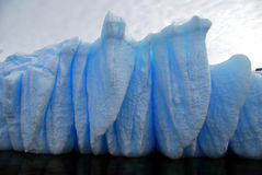 Blue iceberg grooves. Blue iceberg shaped like teeth, dark sea Stock Photo