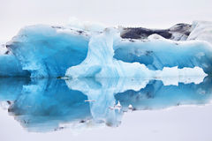 Blue iceberg symmetrically reflected in the water Stock Images