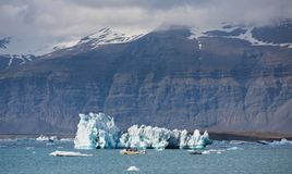 Blue icebergs, lagoon and tourist boat Stock Photos