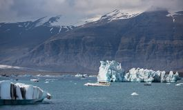 Blue icebergs, lagoon and tourist boat Royalty Free Stock Image