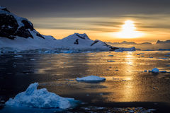 Blue icebergs, mountains and polar sun reflecting in sea lagoon Stock Images